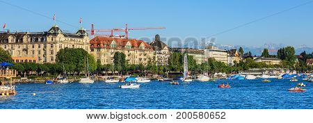 Zurich, Switzerland - 20 July, 2016: Lake Zurich, buildings of the city of Zurich along the lake, people on its embankment, summits of the Alps in the background. Lake Zurich is a lake in Switzerland, extending southeast of the city of Zurich.