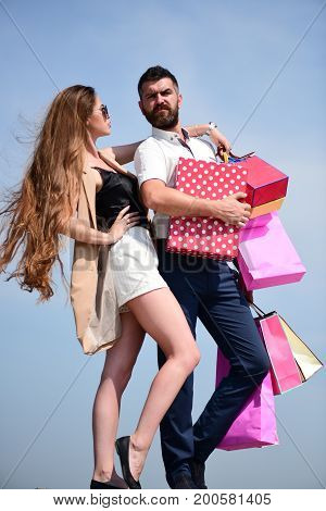 Man with beard and long haired woman hold shopping bags. Couple carries pink packets and box on blue sky background. Shopping and relationship concept. Sexy girl and guy with serious faces