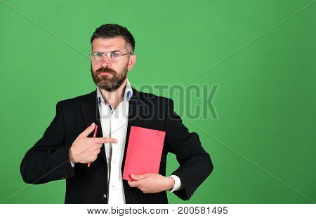 Knowledge and schedule concept. Professor with serious face expression. Notebook in red color in guys hands on green background. Teacher wears glasses and points at organizer. Man with beard and book