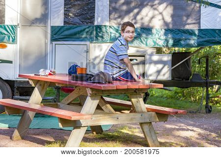 Young preteen boy sitting on picnic table next to family trailer at campsite dappled sunlight though trees happy relaxed expression.