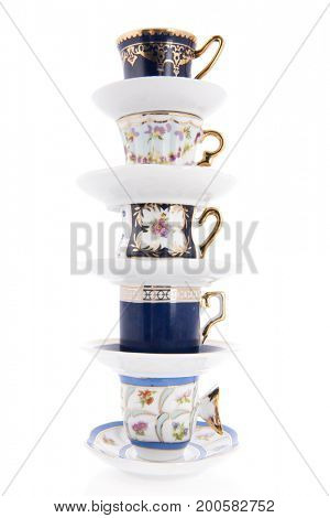 Stacked classic cups and saucers isolated over white background