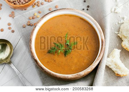 Soup made of lentil and vegetables in a rustic bowl on a canvas tablecloth. Delicious healthy vegetarian food on a white wooden table. Top view.