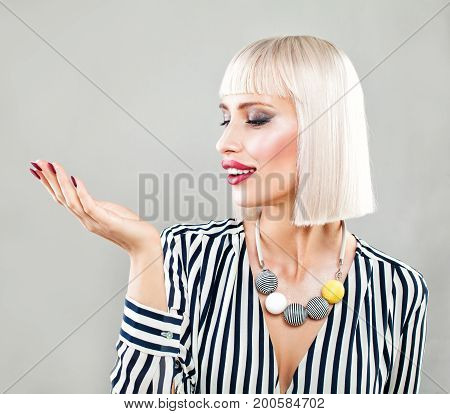 Happy Surprised Woman Showing Empty Copy Space on the Open Hand. Empty Hand Fashion Makeup Blonde Hair