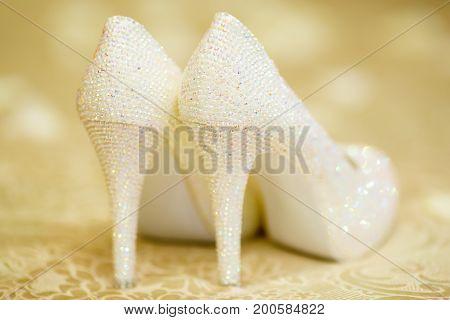 Elegant bridal white shoes with rhinestones on beige background high heels closeup