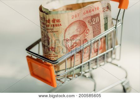 Trolley in a supermarket full of India banknotes. Selective focus on a portrait of Mahatma Gandhi on official currency of the Republic of India