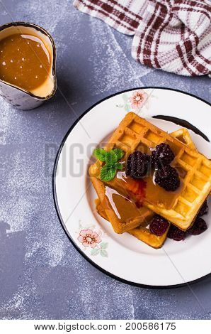 Traditional Belgian waffles with caramel topping and blackberries. Selective focus.