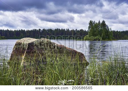Summer landscape with big stone in the lake at gloomy weather. Russia, Karelia