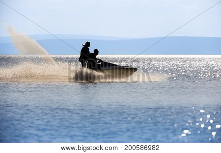 Silhouettes of two people ride the jetski backlit with sun glare