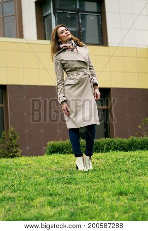 woman in the city in full growth autumn. Stands in front of the building