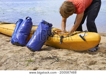 Female hiker inserting a waterproof bag with the things into the kayak