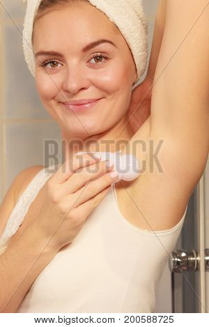 Woman applying stick deodorant in armpit. Girl putting antiperspirant in underarms in bathroom. Daily skin care and hygiene. poster