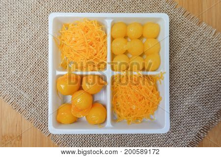 egg yoke fudge balls cooked in syrup bean-paste golden threads - Thai sweet dessert on table - top view
