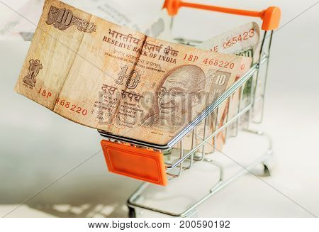Banknotes with indian leader Mahatma Gandhi inside shopping mall trolley. Idea of the consumer ability in modern India.