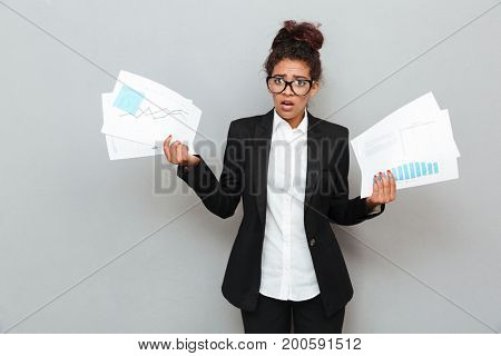 Image of young african confused business woman standing over grey wall with diagramas documents. Looking camera.