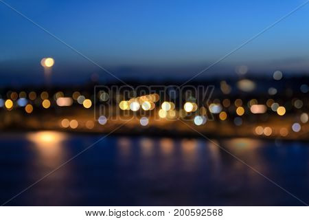 Lights of city coastline with beautiful bokeh effect on the blue sky background in the evening.