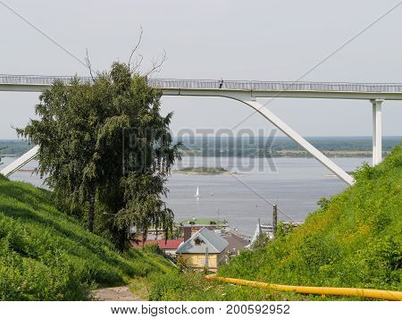 pedestrian bridge over ravine in russian town with big river on background