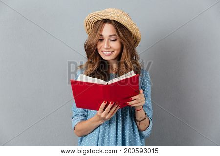 Picture of smiling young pretty woman standing over grey wall wearing hat reading a book. Looking aside.