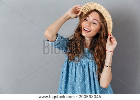 Image of happy young pretty woman standing over grey wall wearing hat. Looking aside.
