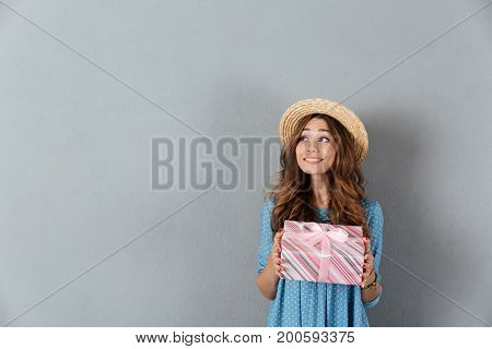 Image of happy young pretty woman standing over grey wall wearing hat holding gift. Looking aside.