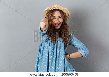 Picture of happy young pretty woman standing over grey wall wearing hat pointing on you. Looking camera.