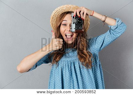 Picture of smiling young caucasian woman photographer holding camera. Showing thumbs up.