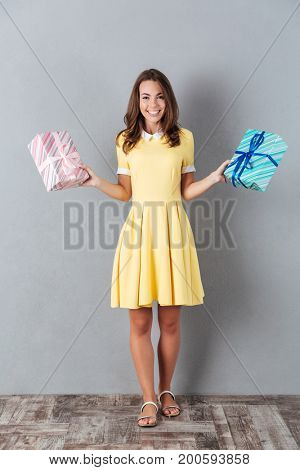 Full length portrait of a happy smiling girl in dress holding two gift boxes while standing isolated over gray background