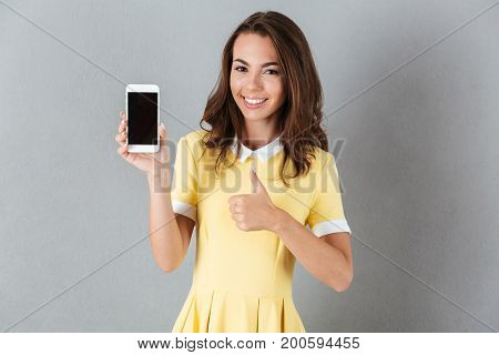Happy young girl showing thumbs up gesture while holding blank screen mobile phone isolated over gray background