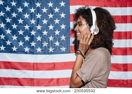 Picture of smiling african young woman standing over USA flag listening music in headphones. Looking aside.