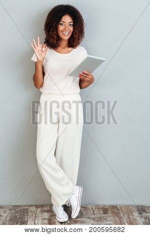 Full length of a cheerful young afro american woman standing with tablet computer and showing ok gesture isolated over white background