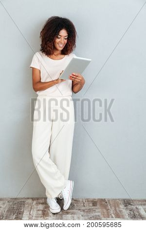 Full length of a pretty young afro american woman standing and using tablet computer isolated over white background