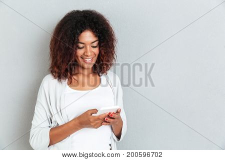 Happy smiling african woman typing message on mobile phone while standing isolated over white background
