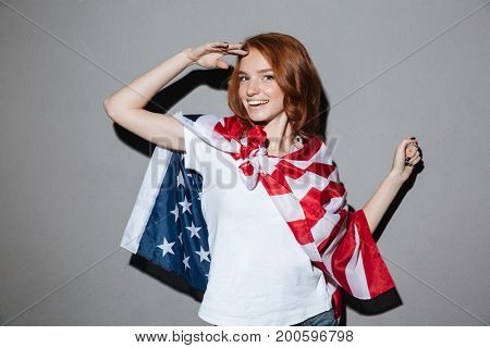 Picture of happy redhead young lady superhero with USA flag. Looking camera.