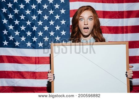 Image of shocked redhead young lady holding copyspace board over USA flag. Looking camera.