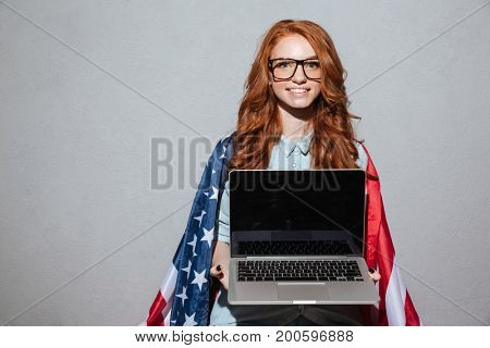Image of cheerful redhead young lady with USA flag showing display of laptop computer. Looking camera.