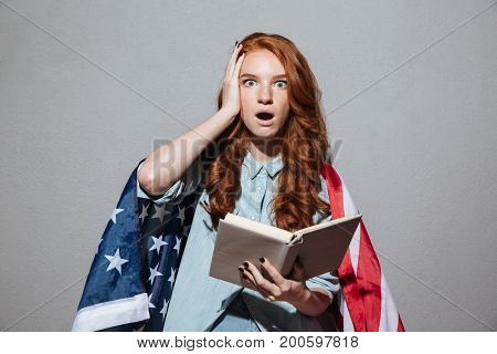 Picture of shocked redhead young lady reading book wearing USA flag. Looking camera.