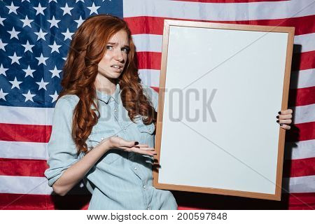 Image of confused redhead young lady holding copyspace board over USA flag. Looking camera.
