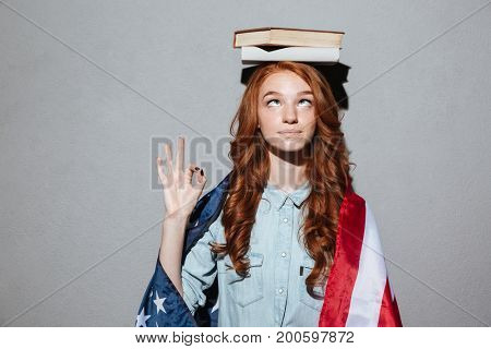 Picture of funny redhead young lady holding book on head wearing USA flag. Looking aside showing okay gesture.