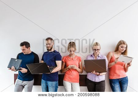 Education social media concept. Male and female diversity students young people studying using computer tablet smartphone standing on wall with copy space