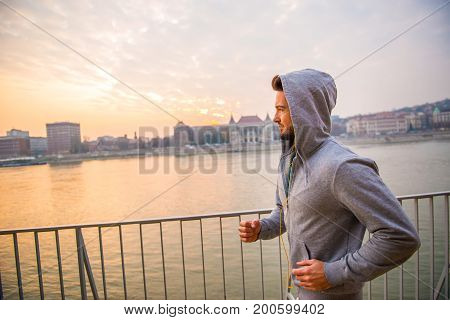 A handsome young man running at the riverside in the sunset