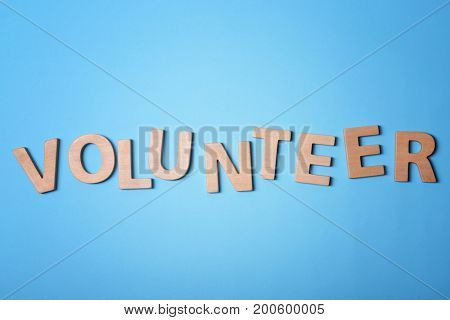 Word VOLUNTEER made of wooden letters on color background