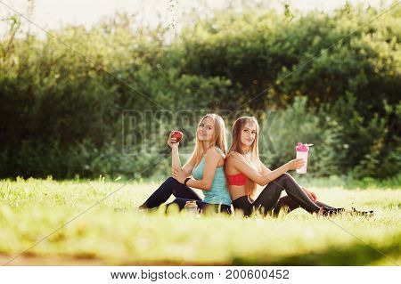 Girlfriends two girls are sitting on grass in park holding an apple and bottle of water to replenish their strength after training on fitness and yoga. Concept of proper nutrition, friendship, outdoor recreation, healthy foods, happy smiles.