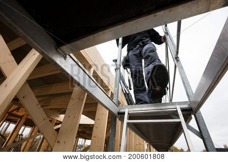 Male Carpenter Moving Down Ladder At Incomplete Building