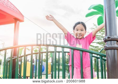 Happy asian girl playing on children playground in park Healthy and recreation concept