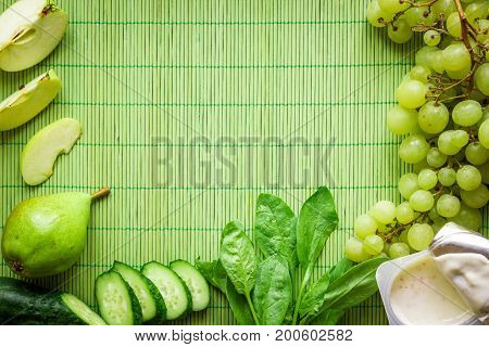 Ingredients for Green detox smoothie. Spinach, grape, yogurt, cucumber and apples on green background. Flat lay with place for text. Vegan and healthy food concept