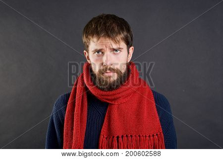 Man with a beard on a black background in a scarf, illness, sick, flu.