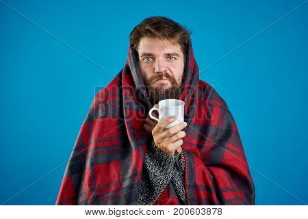 A man with a beard on a blue background in a plaid holds a mug, sickness, sick, flu.
