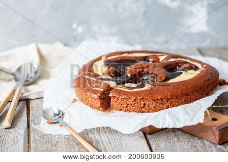 Creamy chocolate cake (biscuit) on a wooden background.