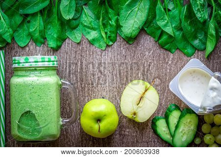Green smoothie with apples, yogurt, spinach, cucumber on wooden background. Flat lay with place for text. Vegan and healthy food concept