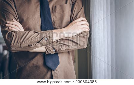 Businessman standing thinking and cross one's arm near window.