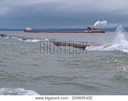 A fully-loaded Great Lakes freighter is steaming past the Presque Isle Breakwater in the quiet waters of the harbor in Marquette, Michigan. It is sailing toward the choppy waters of Lake Superior .